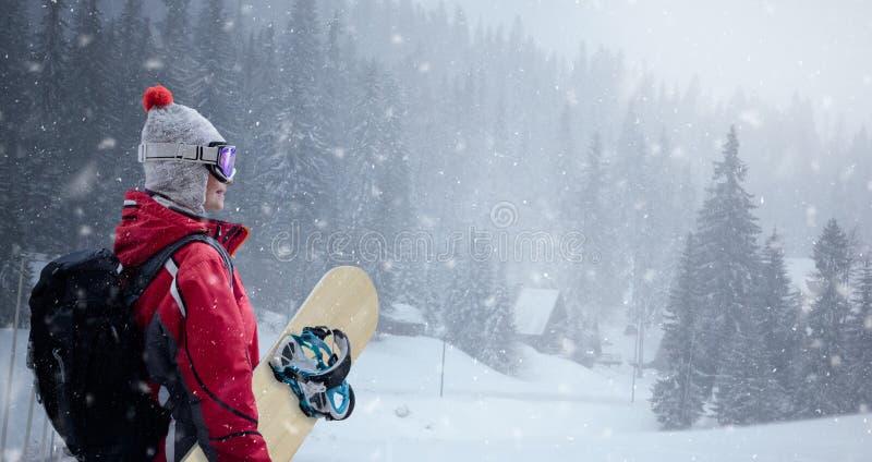 Женщина в костюме лыжи над предпосылкой зимы стоковое изображение