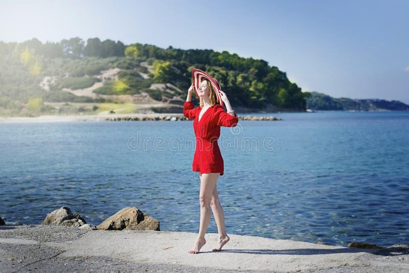 Женщина в красной наслаждаясь солнечности стоковое фото rf