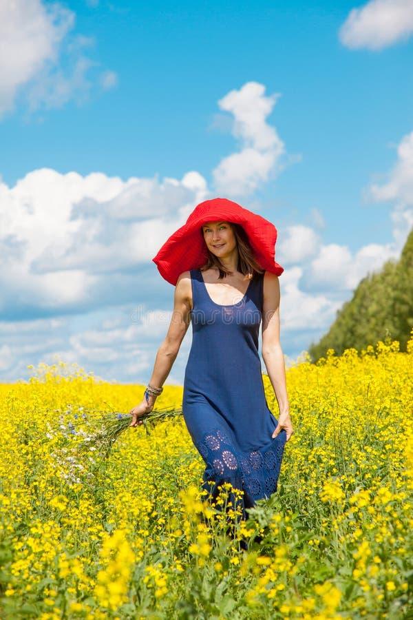 Женщина в красной шляпе и букет полевых цветков стоковое фото