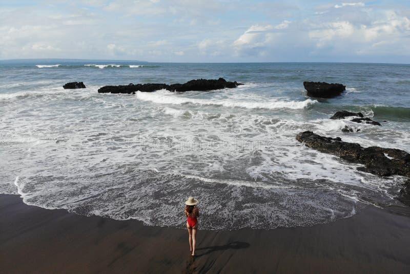 Женщина в красном бикини наслаждается летним днем около океана Каникулы в Бали Фото от трутня стоковые изображения