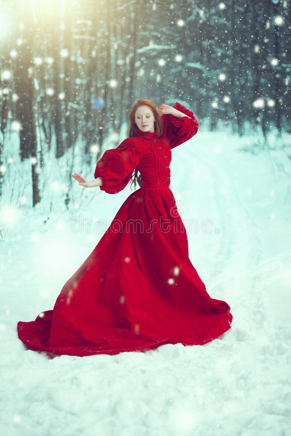 Женщина в красном платье в зиме Девушка сказки над ландшафтом зимы стоковое изображение rf