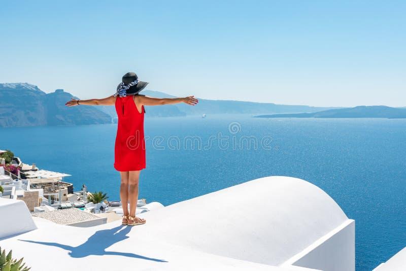 Женщина в красном платье на крыше наслаждаясь взглядом острова и кальдеры Santorini в Эгейском море стоковое фото rf