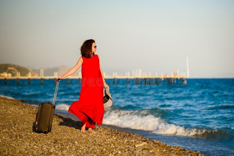 Женщина в красном платье с морем чемодана стоковые фото
