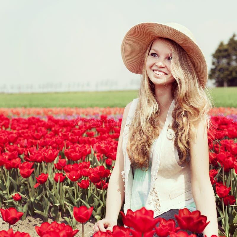 Женщина в красном поле тюльпана стоковые изображения