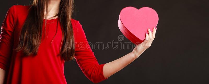Женщина в красном платье держа коробку сердца стоковая фотография