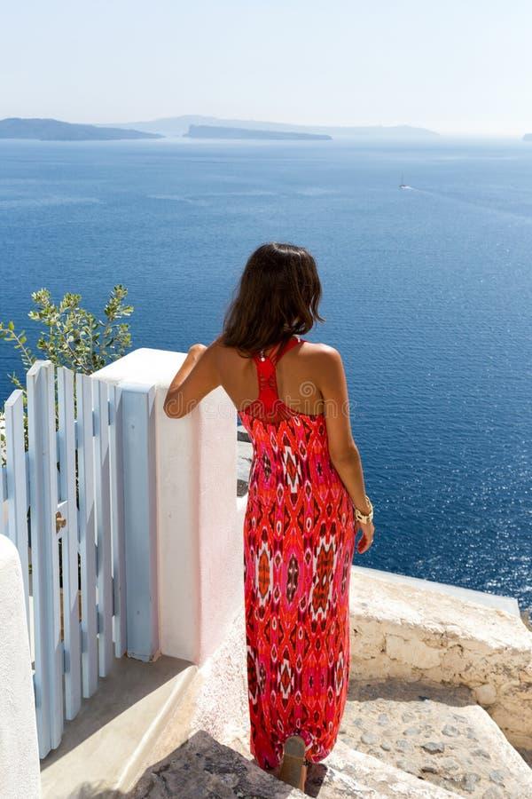 Женщина в красном платье наблюдая море стоковое изображение