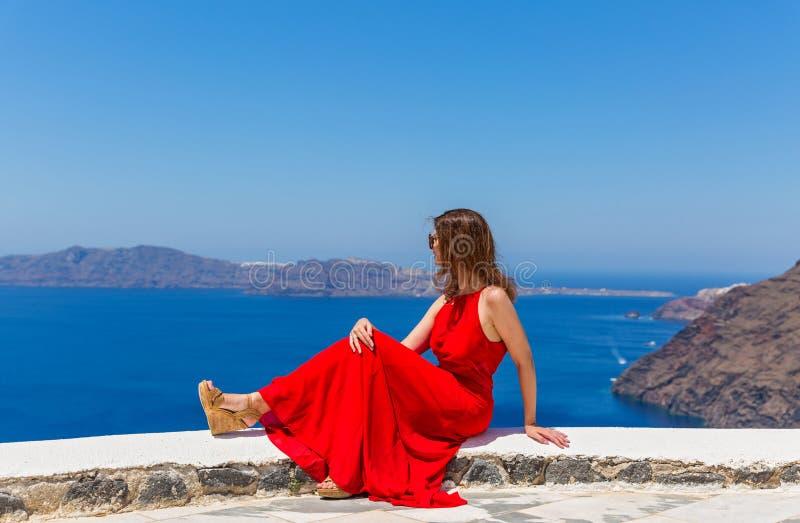 Женщина в красном платье на предпосылке моря стоковые фотографии rf