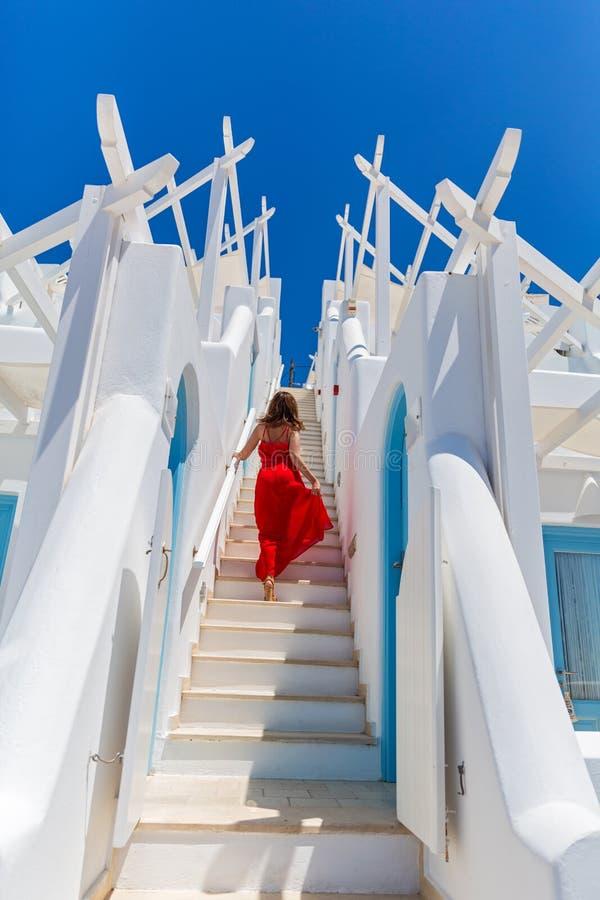 Женщина в красном платье приходя вверх по лестницам стоковое фото