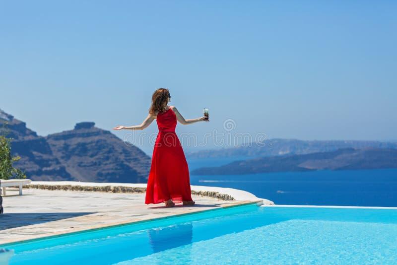 Женщина в красном платье смотрит море стоковые фотографии rf