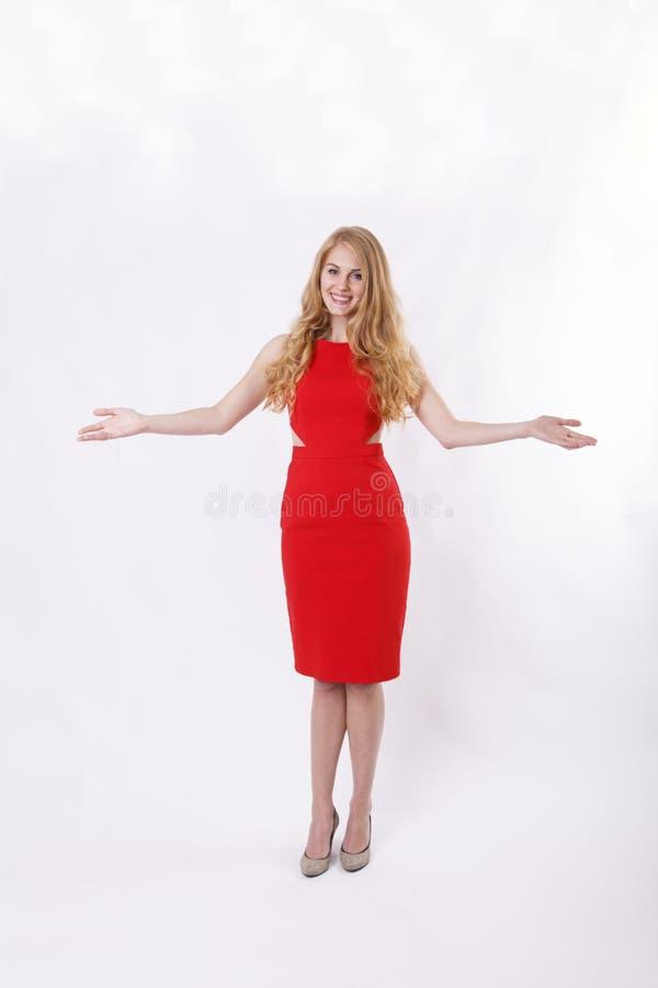 Женщина в красном платья руки гостеприимсве широко открытом стоковое фото