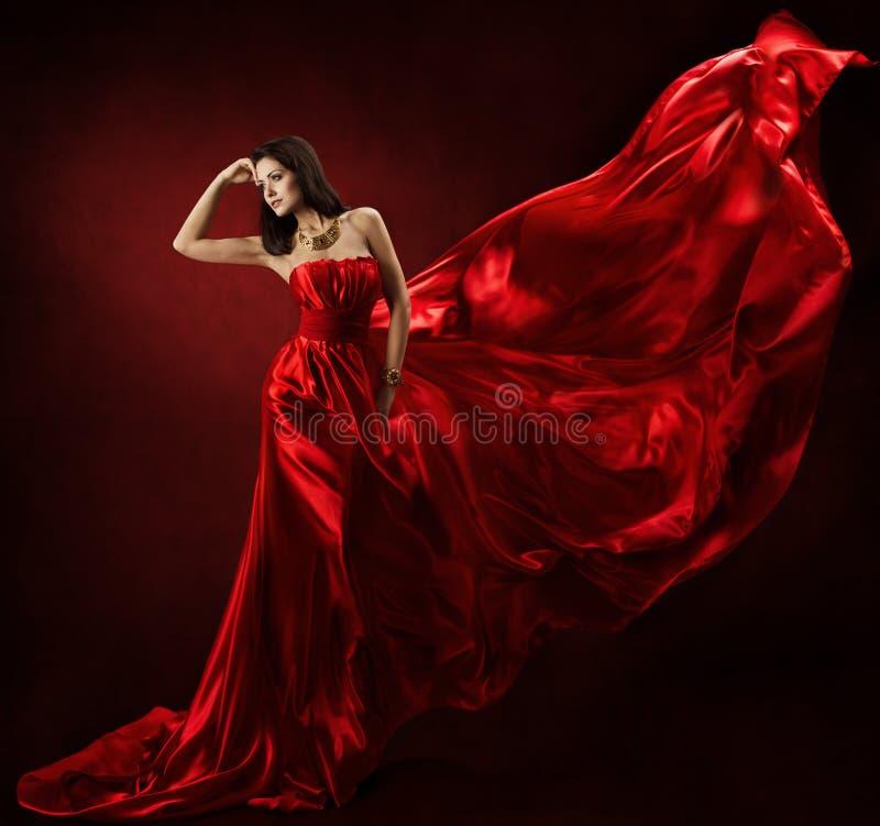 Женщина в красном развевая платье с тканью летания стоковое фото rf
