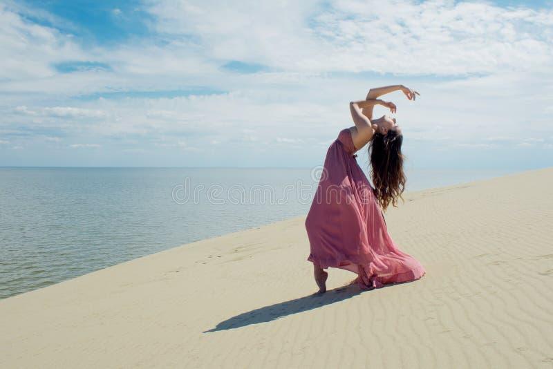 Женщина в красном развевая платье с тканью летания бежит на предпосылке дюн Гимнаст на задней части дюны стоковая фотография