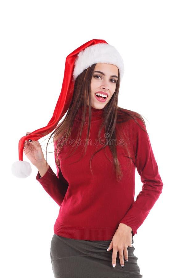 Женщина в красном свитере и шляпе ` s santa представляя пока стоять, держа руку над пушистой шляпой и усмехаться помпона изолиров стоковое фото rf