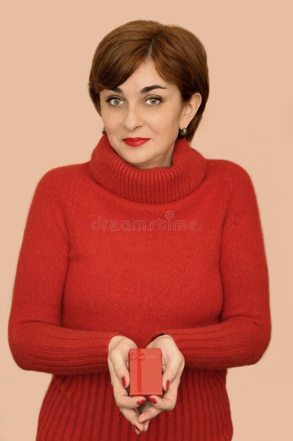 Женщина в красном цвете держа подарок стоковые фотографии rf
