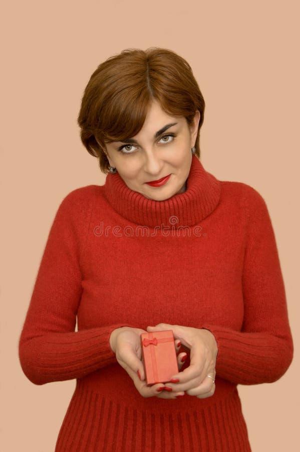 Женщина в красном цвете держа подарок стоковая фотография