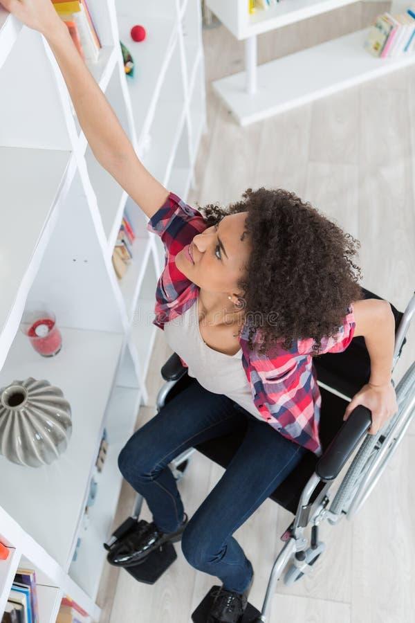 Женщина в кресло-коляске борясь для достижения что-то от полки стоковые изображения rf
