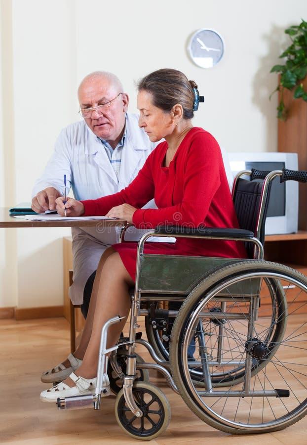 Женщина в кресло-коляске рядом с доктором стоковые фото