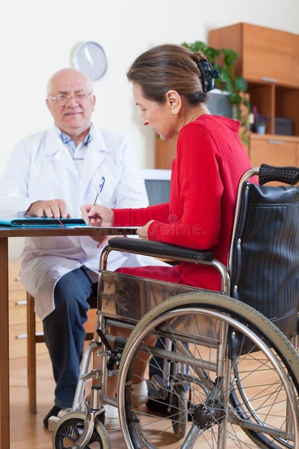 Женщина в кресло-коляске с доктором стоковое фото