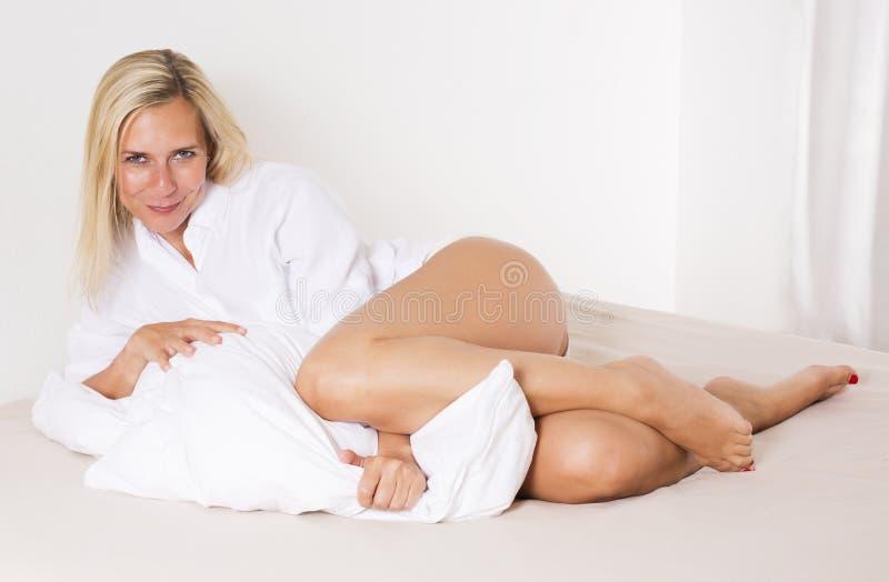 Женщина в кровати ослабляя стоковое фото