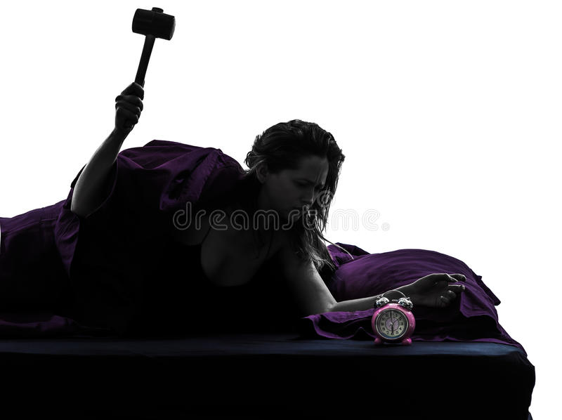Женщина в кровати просыпая вверх ломая силуэт будильника стоковые фотографии rf