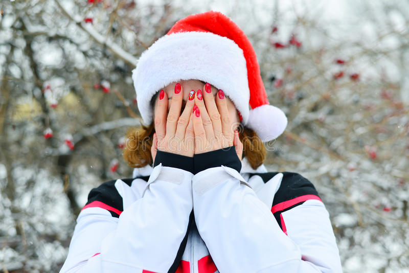 Женщина в крышке Санта Клаусе покрывает ее сторону с ее руками стоковое фото
