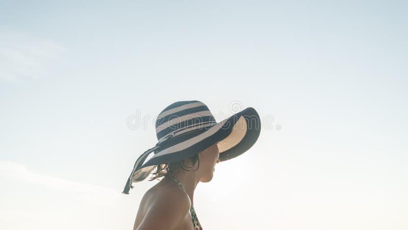 Женщина в купальнике с голубой соломенной шляпой над солнечным небом стоковые фотографии rf
