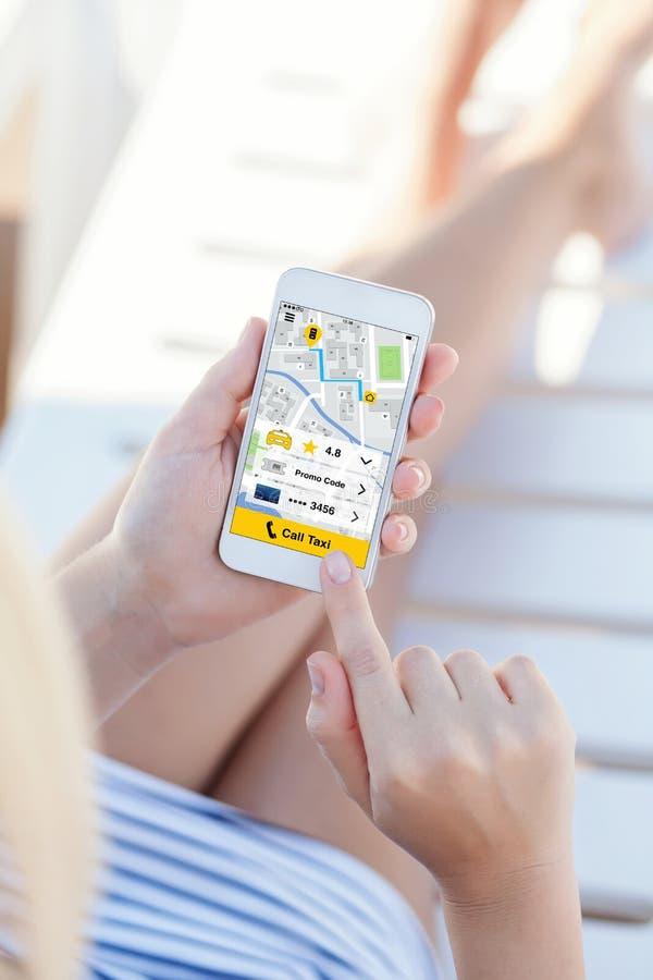 Женщина в купальном костюме держа телефон с такси звонка app стоковые фото
