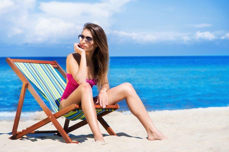 Женщина в купальнике ослабляя на пляже стоковые изображения