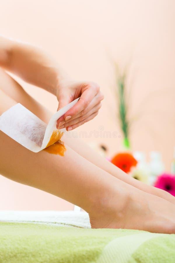 Женщина в курорте получая ногу навощенный стоковое изображение