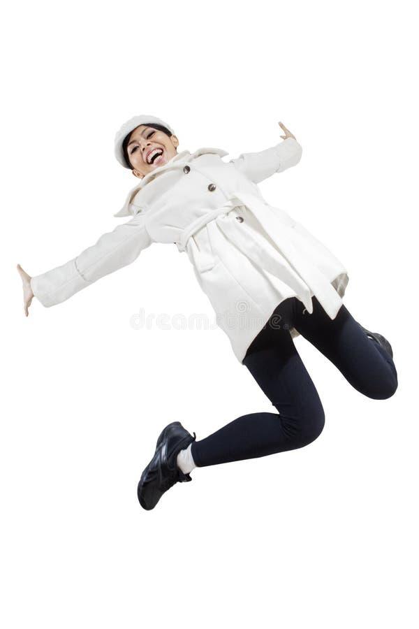 Женщина в куртке зимы скача в студию стоковое фото rf