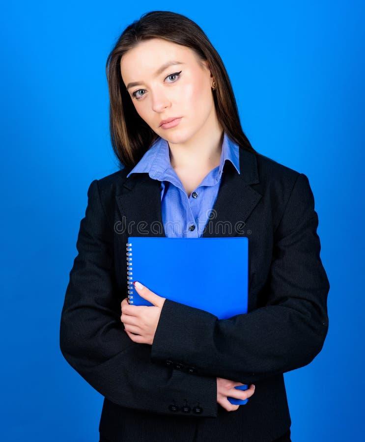 Женщина в куртке с бумажными примечаниями подготавливайте для урока E коммерсантка жизнь студента Умная красота девушка болвана стоковые фото