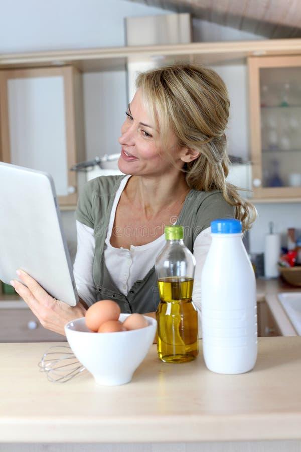 Женщина в кухне варя и ища для рецепта стоковые изображения rf