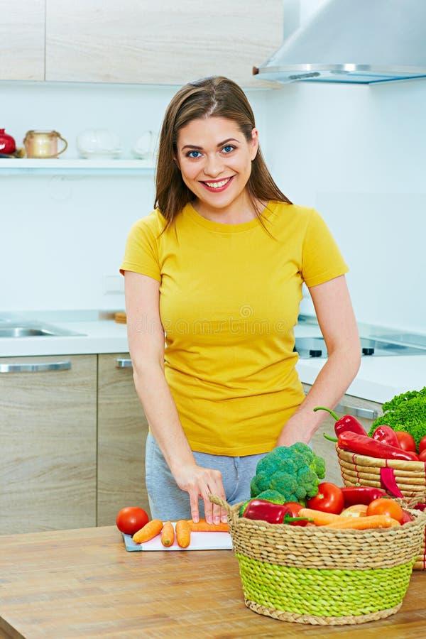 Женщина в кухне варя овощи сь детеныши женщины стоковые фото