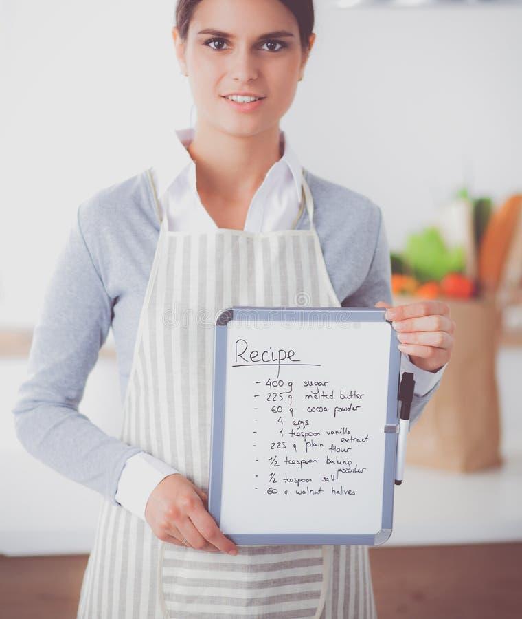 Женщина в кухне дома, стоящ близко стол с папкой стоковое изображение rf