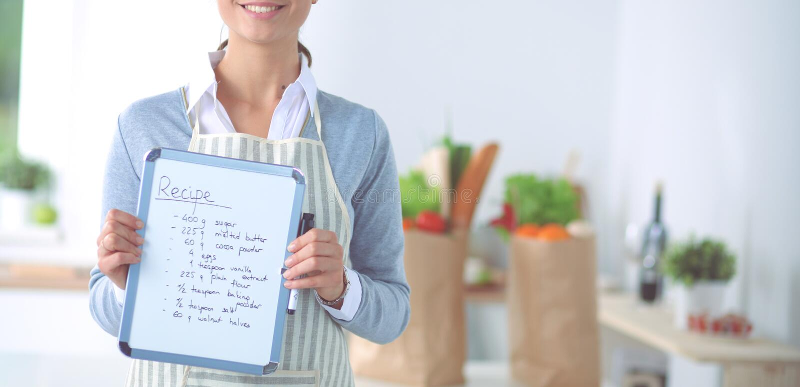 Женщина в кухне дома, стоящ около стола с папкой стоковая фотография