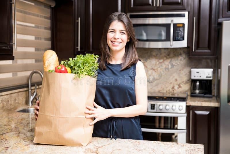 Женщина в кухне с сумкой посещения магазина бакалеи стоковое изображение rf