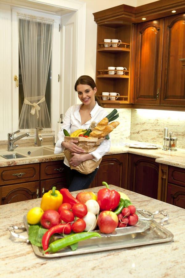 Женщина в кухне с хозяйственной сумкой стоковая фотография
