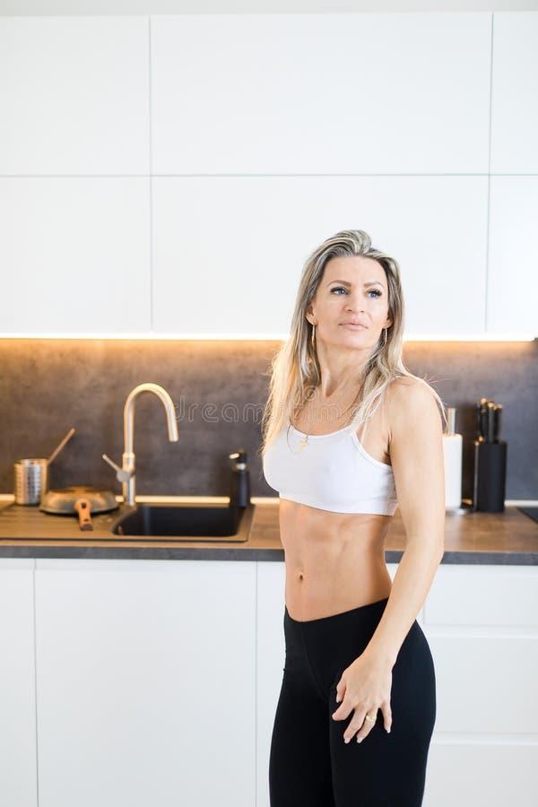 Женщина в кухне - тело фитнеса разминки стоковые изображения