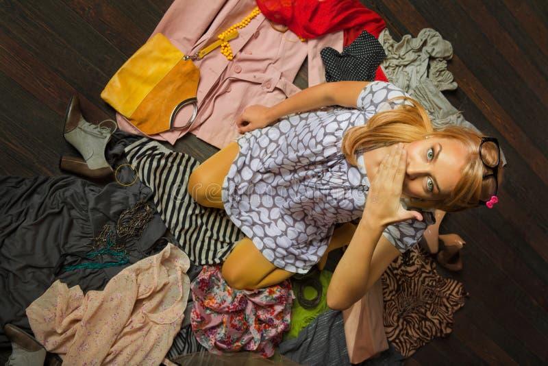 Женщина в куче одежд стоковая фотография rf