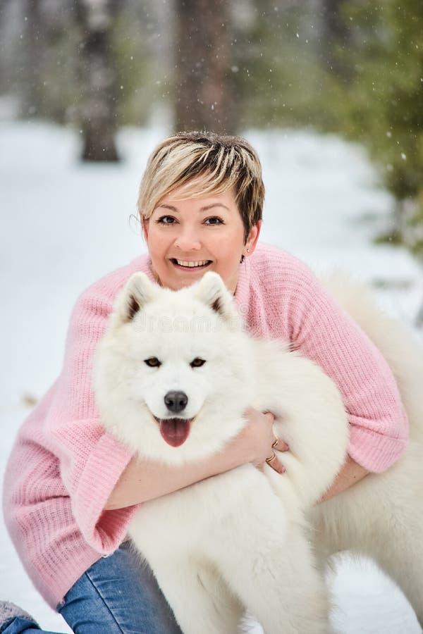 Женщина в лесе зимы идя с собакой Снежок падает стоковое изображение rf