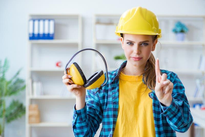 Женщина в мастерской при шум отменяя наушники стоковые фотографии rf