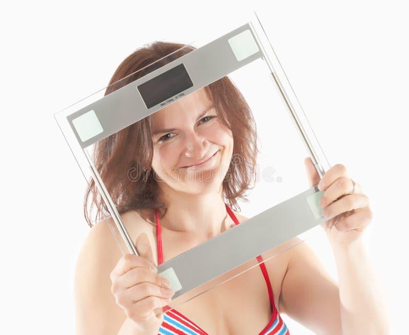 Женщина в масштабе удерживания бикини стоковое изображение
