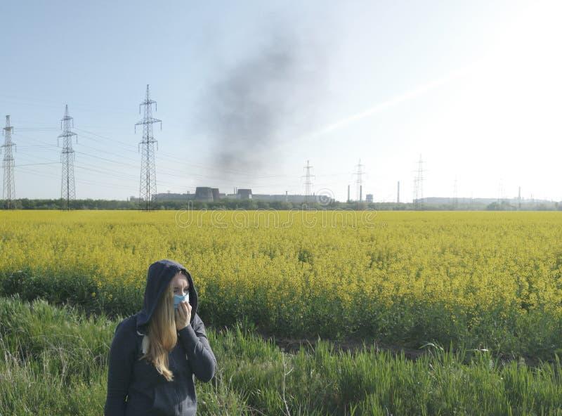 Женщина в медицинской маске на фоне завода Концепция загрязнения окружающей среды, экологичности стоковая фотография rf