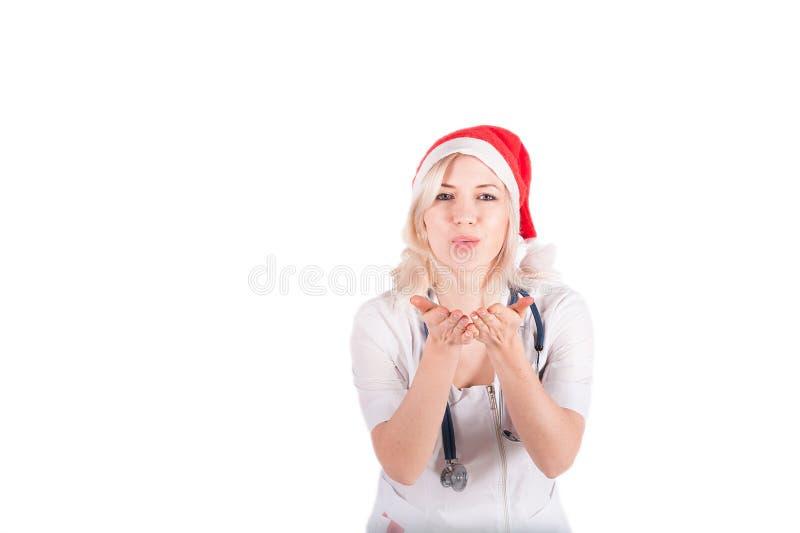 Женщина в медицинском костюме с стетоскопом посылает поцелуй воздуха Врачуйте девушку в шляпе Санта Клауса изолированной на белой стоковые изображения rf