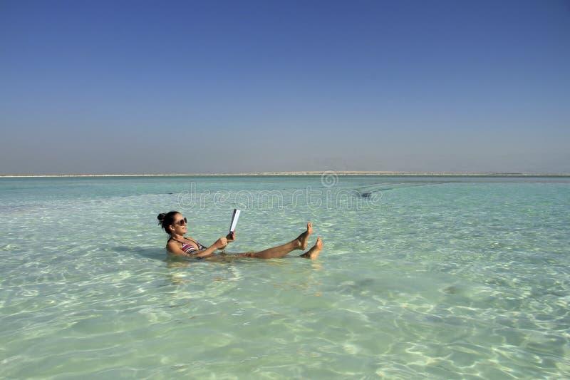 Женщина в мертвом море лежит в воде с книгой и усмехаться стоковые изображения