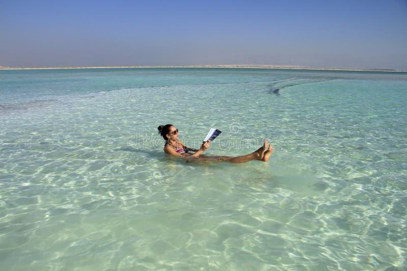 Женщина в мертвом море лежит в воде стоковые фото