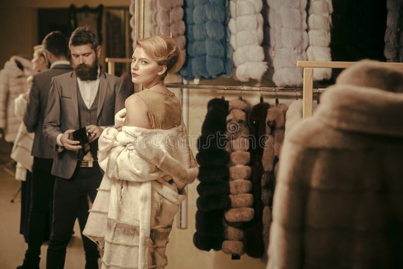 Женщина в меховой шыбе с человеком, покупками, продавцем и клиентом стоковое фото rf