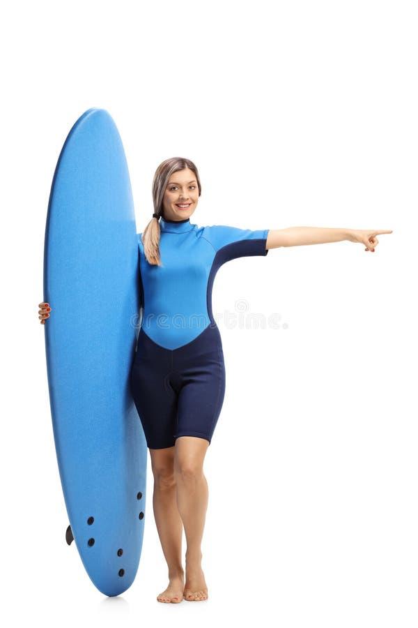 Женщина в мокрой одежде держа surfboard и указывать стоковые изображения