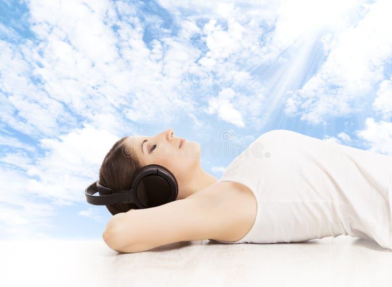 Женщина в наушниках мечтая слушать к музыке девушка ослабляя стоковые изображения