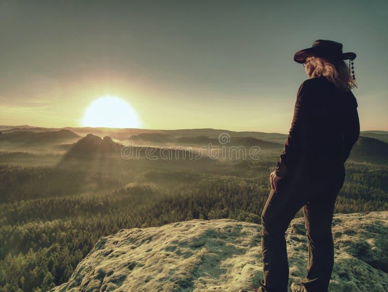 Женщина в на открытом воздухе одеждах наслаждается взглядом на саммите в горах стоковые фото
